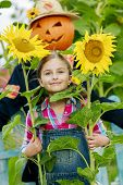 Scarecrow and happy girl  in the garden - Autumn harvests