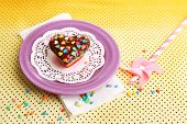 Delicious rainbow mini cake on colorful plate, on bright background