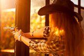 Young woman cowboy shooting. Focus on gun.
