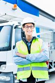 Female engineer standing in front of truck on building or construction site
