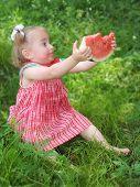 little girl eats watermelon with pleasure