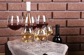 Bottle and glasses of wine on table on brick wall background