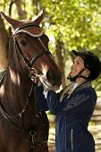 pic of horse-riders  - Young female rider looking at horse with love - JPG