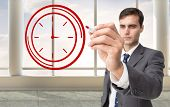 Composite image of business person drawing a red clock