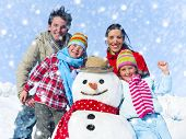 Family posing with a snowman outdoors.