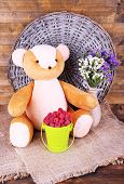 Toy bear, bucket of raspberries and vase of field flowers on sackcloth on wooden wall background