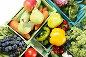 Fresh organic vegetables and fruits in wooden boxes, close up