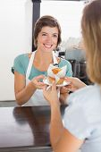 Pretty waitress serving muffin to customer at the coffee shop