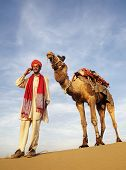 Global communications. Indian Guide and camel (Jonnie) in the desert.