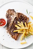 T-bone Steak With Salted French Fries On White Plate On Blue Wooden Background