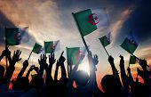 Silhouettes of People Holding Flag of Algeria