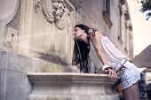 young girl drinking water from a fountain