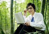 Businessman sitting in a bamboo forest.