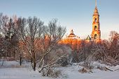 Beautiful winter sunset in the forest and church