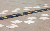 picture of retarded  - Traffic safety speed bump on an asphalt road - JPG