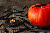 pic of horrifying  - big pumpkin on the table where scattered black feathers and lit candle - JPG