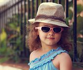 Modern Kid Girl In Fashion Glasses And Hat Looking Happy On Summer Background