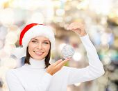 winter, people, happiness concept - woman in santa helper hat with christmas tree decoration over li