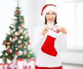christmas, winter, happiness, holidays and people concept - smiling woman in santa helper hat with small gift box and stocking over living room and christmas tree background