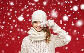 winter, people, happiness concept - smiling girl in hat, muffler and gloves with big snowflake