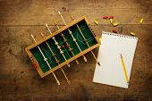 Mini soccer game and a blank note pad, on an old wooden table. Tactics, game planning concept.