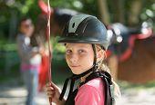 Young girl in horseback rider helmet
