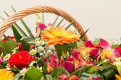 Bouquet of multi-colored flowers in a wattled basket