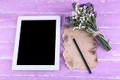 Tablet, bunch of flowers and piece of paper and pencil on wooden background