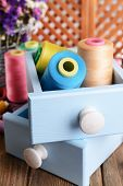 Sewing Accessories in wooden boxes on table on brown background