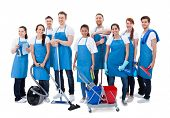 image of collaboration  - Large diverse group of janitors wearing blue aprons standing grouped together with their equipment smiling at the camera isolated on white - JPG