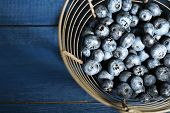 Tasty ripe blueberries in metal basket, on wooden background