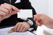 Businessman Giving Business Card To Colleague