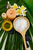 spa setting with salt in spoon and towel,candle,massage oil on palm texture