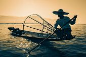Myanmar travel attraction landmark - Traditional Burmese fisherman at Inle lake, Myanmar famous for their distinctive one legged rowing style