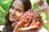 Beautiful slender girl eating healthy fruit. Portrait of pretty young woman holding ripe grapes bunch