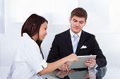Doctor Showing Digital Tablet To Businessman
