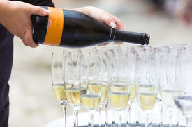 image of banquet  - Banquet event. Waiter pouring champagne into glass. ** Note: Shallow depth of field - JPG