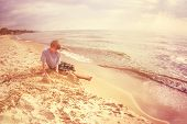 Dreamy image of a boy building a sandcastle on the beach. Instagram effect.