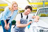 Male mechanic examine car finish on dents or scratches in workshop