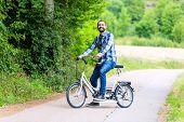 Man riding tandem bike on country lane