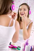 Teenage girl applying make up and looking in the mirror, pretty teens having fun and putting makeup lipstick or lip gloss, joyful teenager