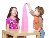 Brother and sister collects Red Pyramid in the Montessori kinder