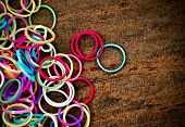 Colorful Rainbow Loom Bracelet Rubber Bands Fashion On Old Wood Background With Space On The Left