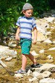 The Kid Plays Near A Mountain Stream