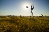 stock photo of windmills  - A windmill stands silouhetted in a wheat field in outback rural Australia the road can be seen to the left.