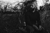 bearded lumberjack resting on stump