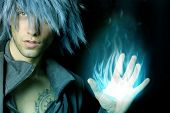 stock photo of warlock  - handsome sorcerer that creates a blue fireball with his hand - JPG