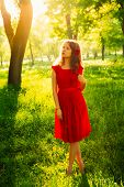 Pretty Young Women In Red Dress Backlit By Sunset In Front Of Green Trees.