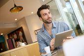 Man websurfing on digital tablet in coffee shop