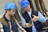 stock photo of engineering construction  - Engineer with mechanical worker checking on production - JPG